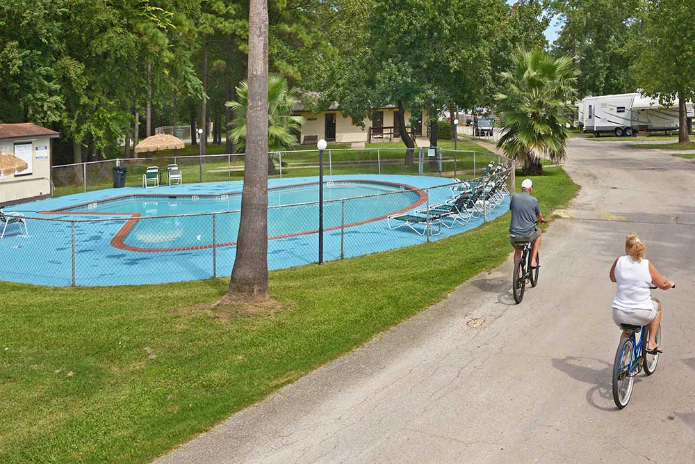 bikers riding past a pool