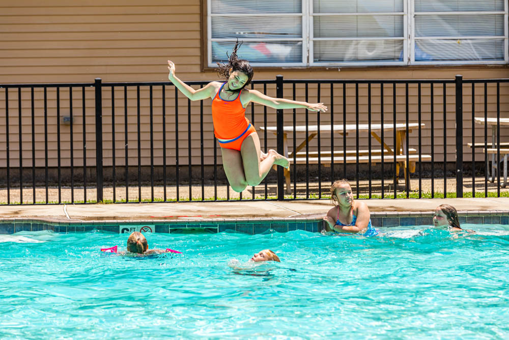 girl jumping into a pool
